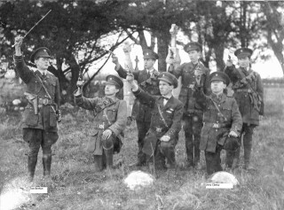 Members of the Ballygar Volunteers firing shots in Killeroran graveyard. circa 1916. Jerry Clancy (O/C) is kneeling in front at the far right. Tom Brehon is standing on left.